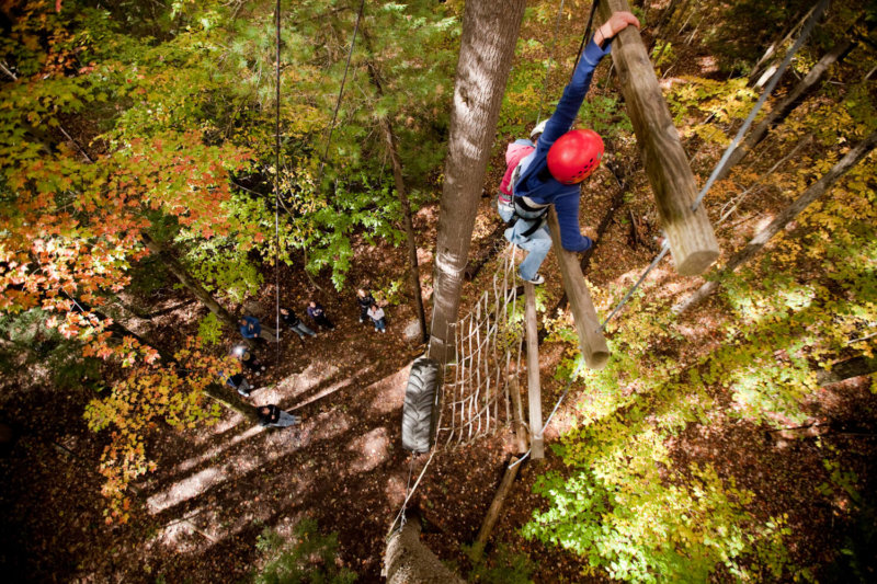 student navigating ropes course in the fall