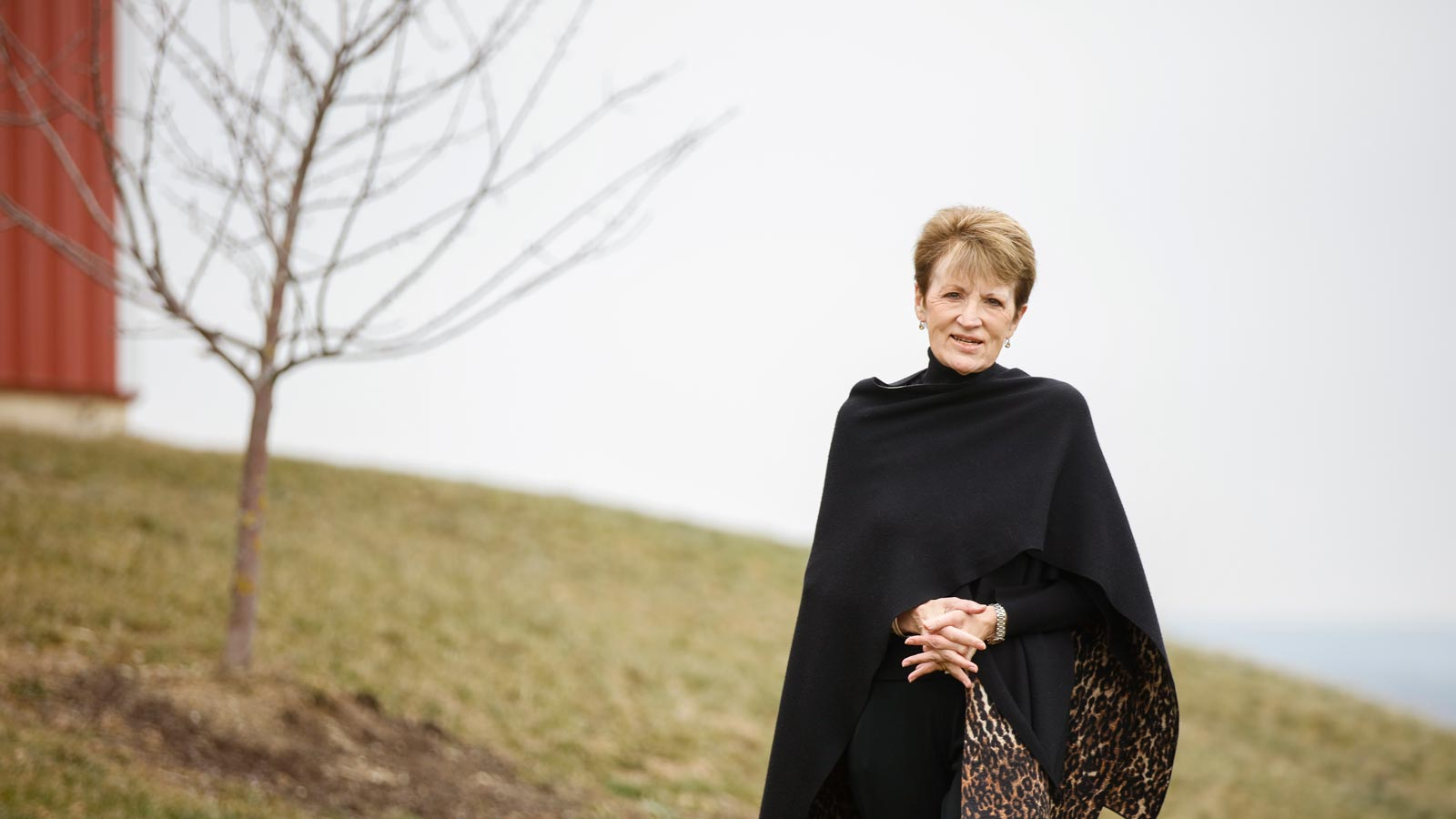 Shirley Mullen standing next to the Equestrian Center at Houghton College