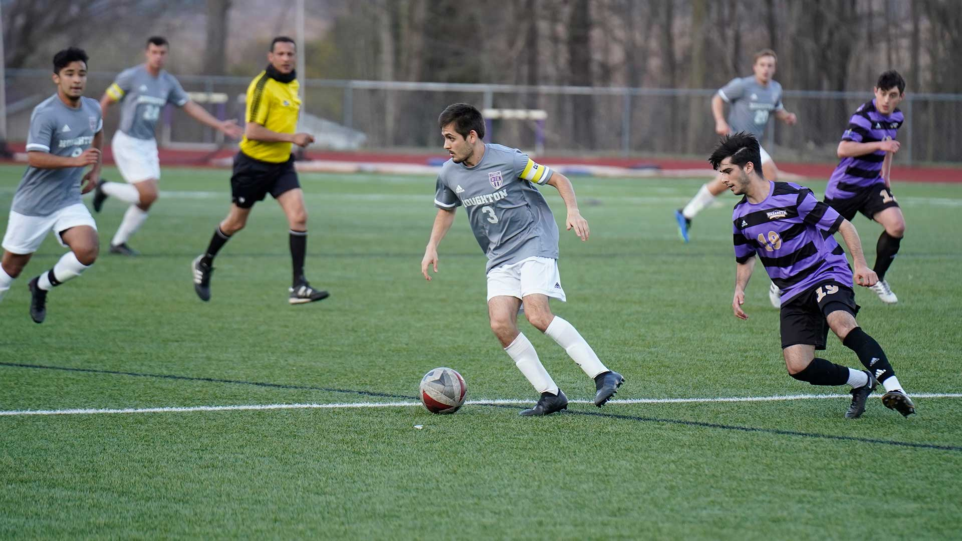 men's soccer player running with ball on field