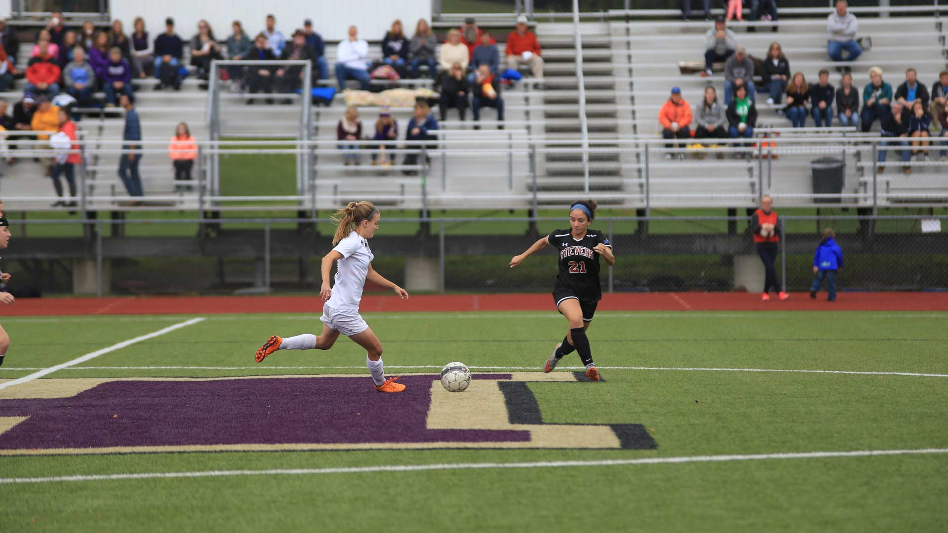 Houghton Women Soccer Player Running with ball across midfield line