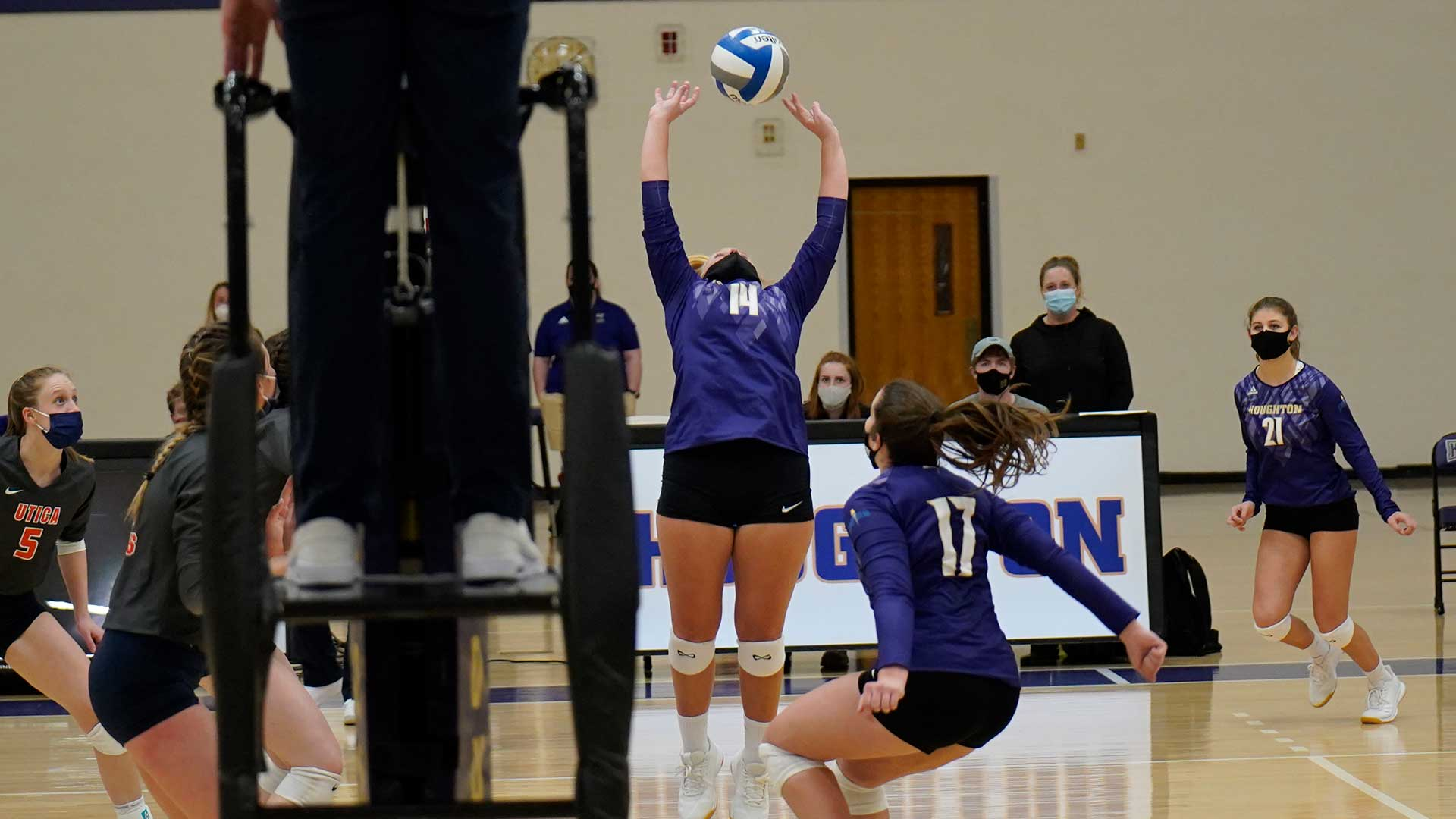 women's volleyball player setting the ball at the net